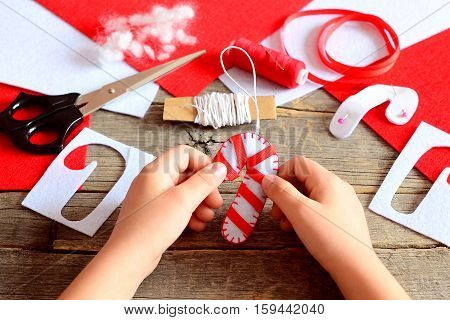 Child holds Christmas felt candy cane in his hands. Materials and tools to create Christmas tree decorations. Simple and beautiful handicrafts concept. Kids Christmas DIY idea. Vintage style