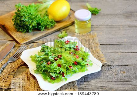 Healthy lettuce with pomegranate dressed with lemon juice and olive oil. Bright easy vegetarian salad. Light salad on a plate, ingredients, fork, knife on wooden background with copy place for text