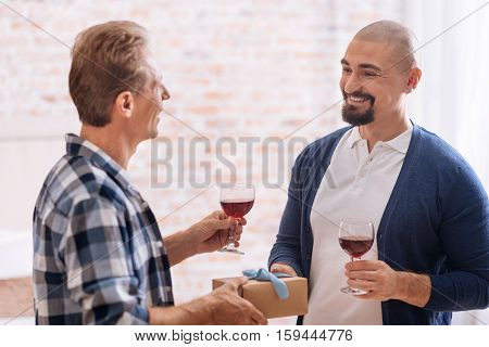 It is for you my dear. Smiling positive cheerful non-traditional couple standing in the bedroom and drinking wine while expressing happiness and giving presents to each other