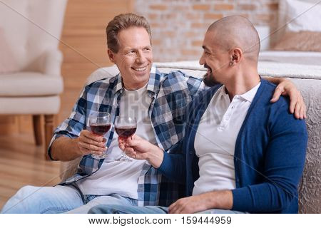 We enjoying our love. Smiling happy delighted non-traditional couple sitting in the bedroom and drinking wine while expressing happiness and hugging each other