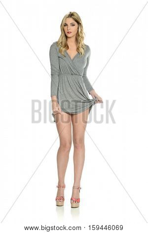 Young blond fashion model with short dress isolated on a white background