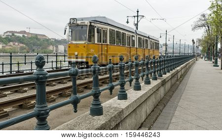 Yellow tramcar in Budapest on a cloudy day