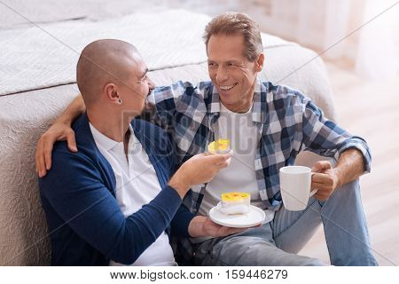 It is so delicious. Smiling cheerful non-traditional couple sitting on the floor in the bedroom and eating bakery while having fun together and drinking tea