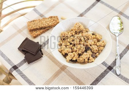 Healthy morning breakfast on the table with tablecloth in the garden. Dark chocolate and granola. Natural light. Good morning mood.