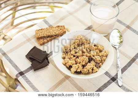 Healthy morning breakfast on the table with tablecloth in the garden. Dark chocolate, granola, sweet cookies and drinking yogurt in the glass. Natural light. Good morning mood.