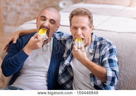We like cakes. Cheerful pleasant positive non-traditional couple sitting on the floor in the bedroom and eating bakery while having fun together
