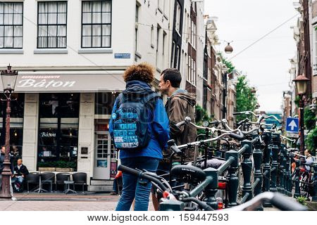 Amsterdam Netherlands - August 2 2016: Travelers in the street in historical city center of Amsterdam. It is one of the most romantic and beautiful cities in Europe. Amsterdam is also a city of tolerance and diversity.