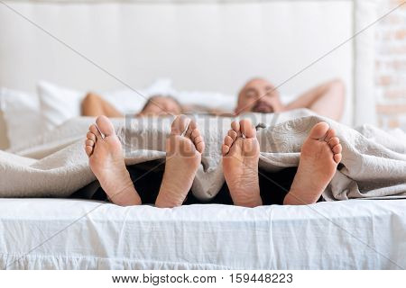 We showing our feet. Cheerful positive pleasant gay couple lying on the bed in the bedroom while expressing love and care and showing their feet under the blanket