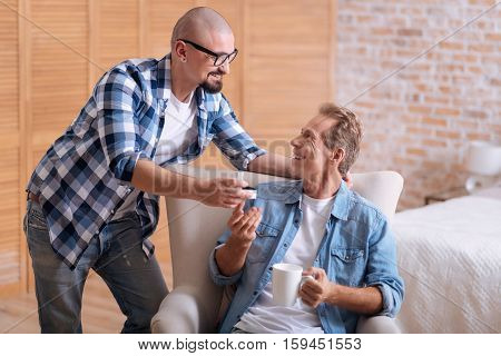 Will you be my love. Happy positive young homosexual man standing in the bedroom and hugging his love while making the proposal and his partner expressing happiness