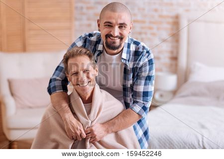 I want to warm you. Happy positive smiling man standing in the bedroom and expressing love and care towards his partner while hugging him and covering with the blanket