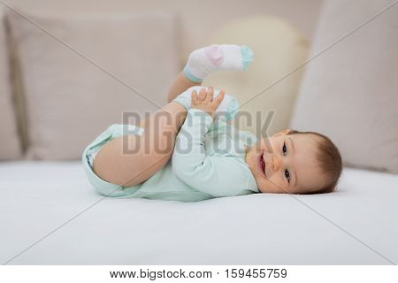 Playful baby lying down in bed. Happy baby lying on white sheet and holding her legs