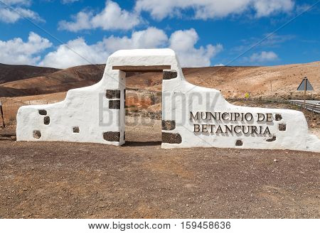 FUERTEVENTURA, SPAIN - SEPTEMBER 15, 2015: Typical municipality sign (white arch gate) near Betancuria village with desert mountain landscape in the background Fuerteventura Canary Islands Spain
