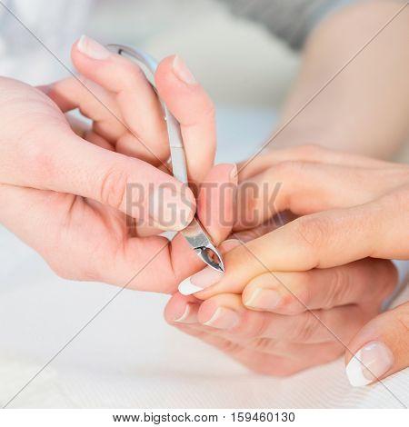 Nipping cuticles at nail salon, toned image, white