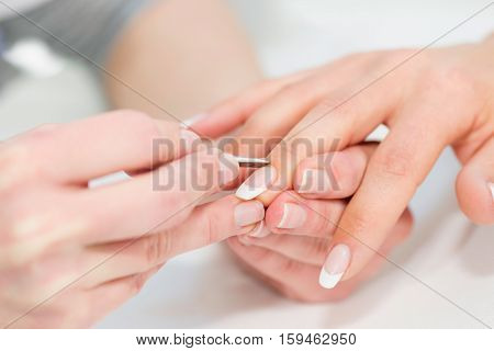manicuring hands - pushing cuticles, white background
