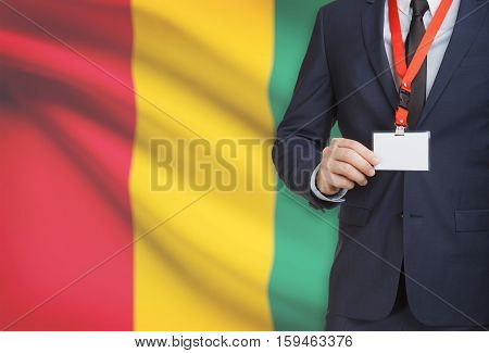 Businessman Holding Name Card Badge On A Lanyard With A National Flag On Background - Guinea