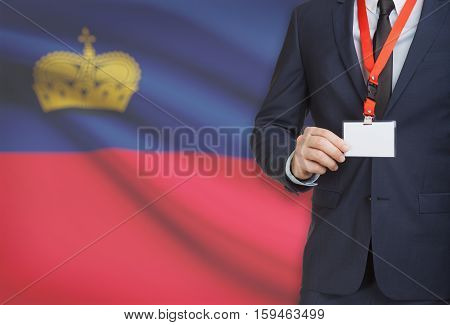 Businessman Holding Name Card Badge On A Lanyard With A National Flag On Background - Liechtenstein