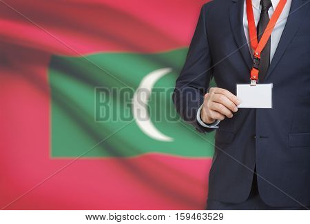 Businessman Holding Name Card Badge On A Lanyard With A National Flag On Background - Maldives