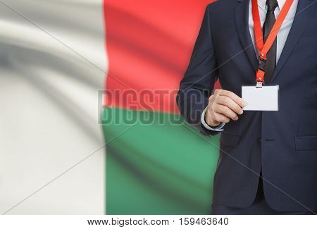 Businessman Holding Name Card Badge On A Lanyard With A National Flag On Background - Madagascar