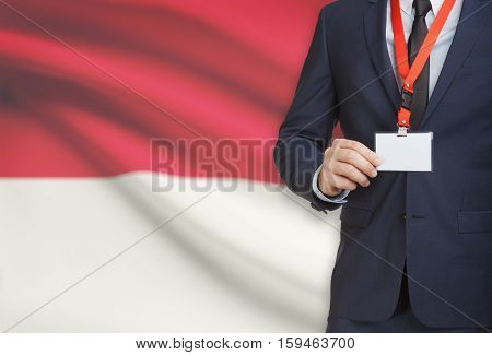 Businessman Holding Name Card Badge On A Lanyard With A National Flag On Background - Monaco