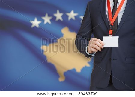 Businessman Holding Name Card Badge On A Lanyard With A National Flag On Background - Kosovo