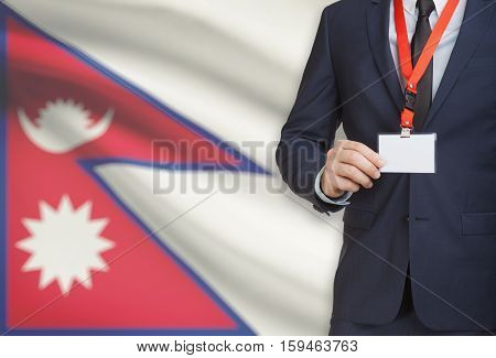 Businessman Holding Name Card Badge On A Lanyard With A National Flag On Background - Nepal