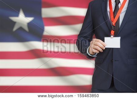 Businessman Holding Name Card Badge On A Lanyard With A National Flag On Background - Liberia