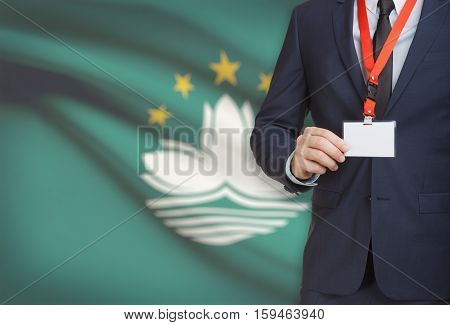 Businessman Holding Name Card Badge On A Lanyard With A National Flag On Background - Macau