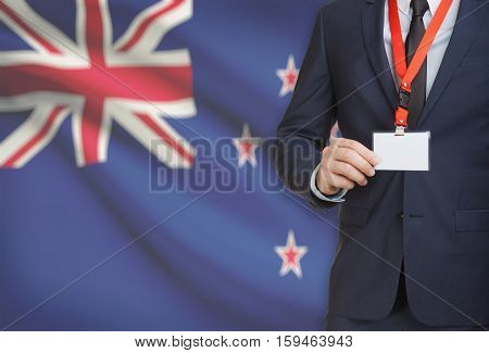 Businessman Holding Name Card Badge On A Lanyard With A National Flag On Background - New Zealand