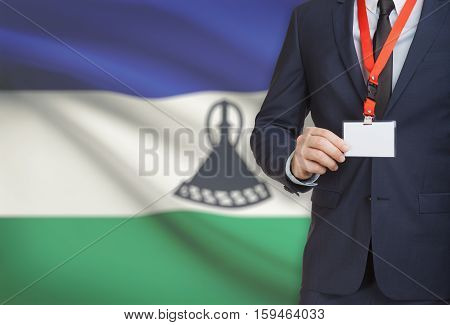 Businessman Holding Name Card Badge On A Lanyard With A National Flag On Background - Lesotho