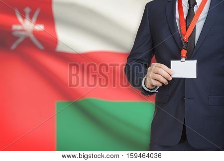 Businessman Holding Name Card Badge On A Lanyard With A National Flag On Background - Oman