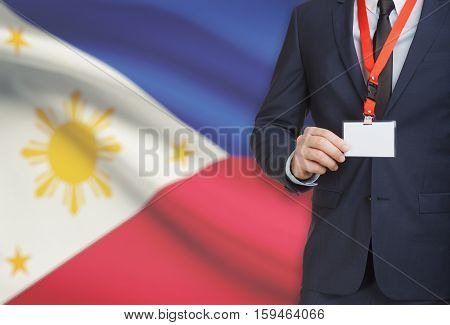 Businessman Holding Name Card Badge On A Lanyard With A National Flag On Background - Philippines
