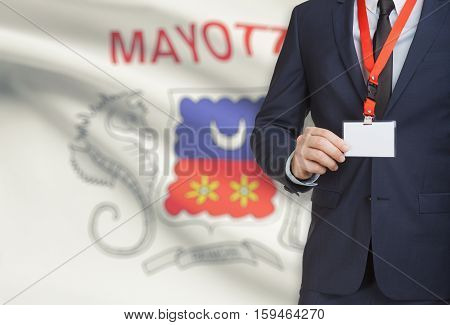Businessman Holding Name Card Badge On A Lanyard With A National Flag On Background - Mayotte