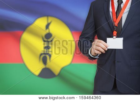 Businessman Holding Name Card Badge On A Lanyard With A National Flag On Background - New Caledonia