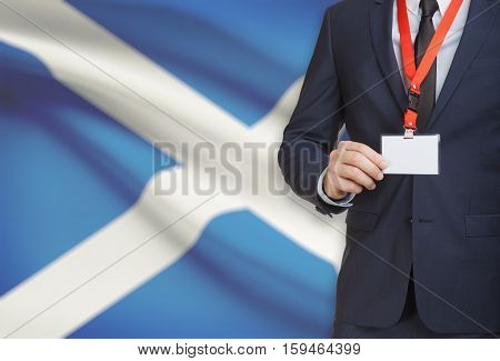 Businessman Holding Name Card Badge On A Lanyard With A National Flag On Background - Scotland