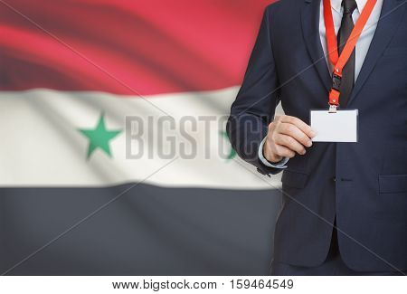 Businessman Holding Name Card Badge On A Lanyard With A National Flag On Background - Syria