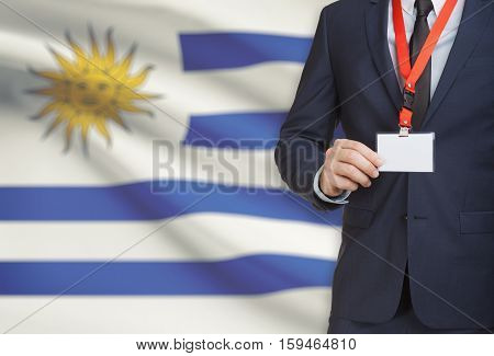 Businessman Holding Name Card Badge On A Lanyard With A National Flag On Background - Uruguay