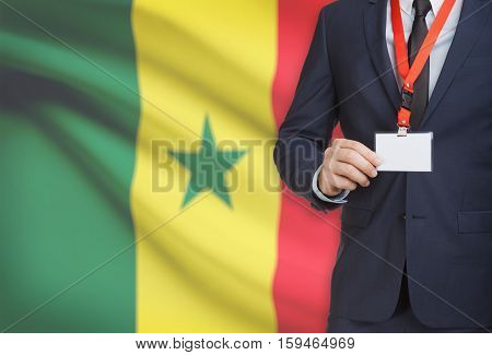 Businessman Holding Name Card Badge On A Lanyard With A National Flag On Background - Senegal