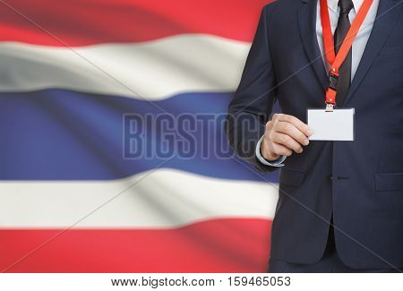 Businessman Holding Name Card Badge On A Lanyard With A National Flag On Background - Thailand