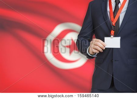 Businessman Holding Name Card Badge On A Lanyard With A National Flag On Background - Tunisia