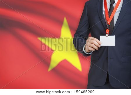 Businessman Holding Name Card Badge On A Lanyard With A National Flag On Background - Vietnam