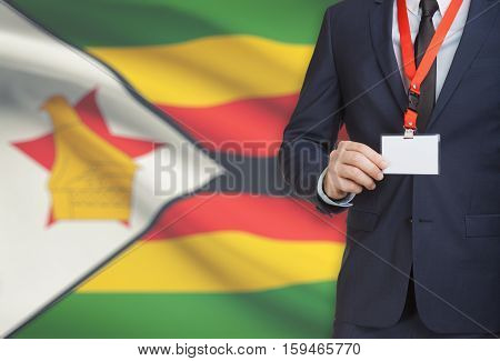 Businessman Holding Name Card Badge On A Lanyard With A National Flag On Background - Zimbabwe