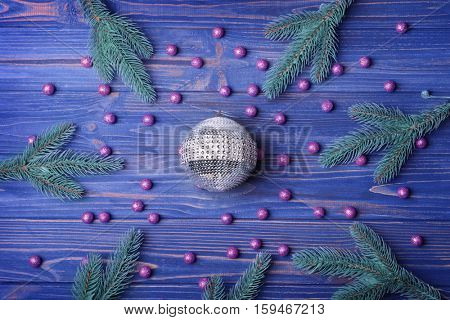 Composition of glass ball, beads and coniferous branches on wooden background