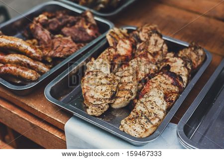 Grill steaks on metal grate. Roasted juicy meat and wurst sausages barbecue. BBQ fresh beef chop slices. Traditional dish on charcoal and flame, picnic, street food