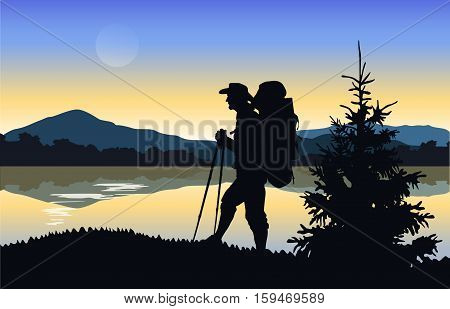 Silhouette of a tourist on a background of mountains and water. Mountain landscape at dawn.