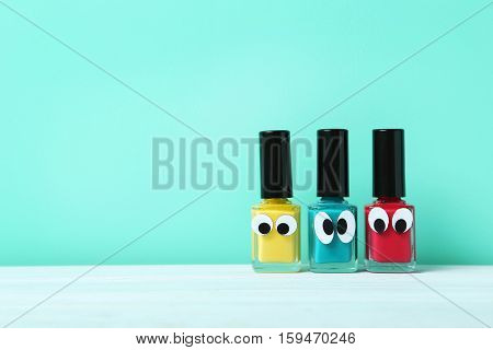 Bottles Of Nail Polish With Googly Eyes On A Green Background