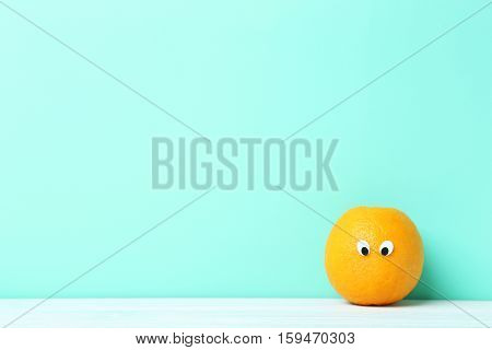 Ripe Orange With Googly Eyes On Green Background