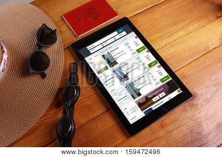 SHAH ALAM 7 OCTOBER 2016. Travel and concept background with a hat sunglasess pasport goggles and digital tablet show trivago travel agency.