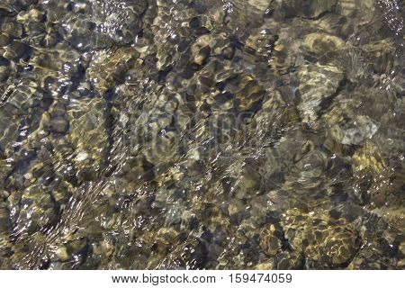 The rocks under the water, looked through through the clean water on a mountain rive