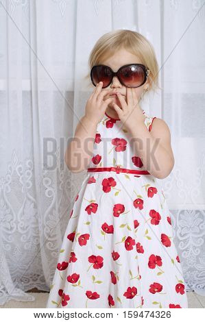 photo of little girl with sunglasses on white