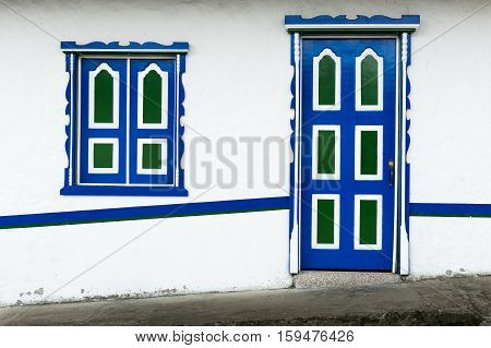 Detail of a wooden door and window painted in bright colors in a traditional colonial house in the town of Salento in Colombia South America; Concept for traveling in South America and Colombia